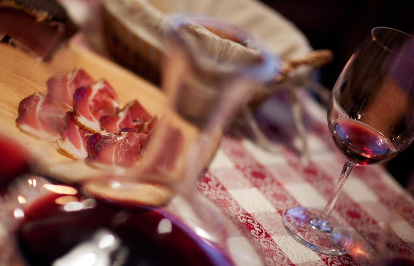 Plate of cured meat with a glass of red wine at Hotel Cavallino