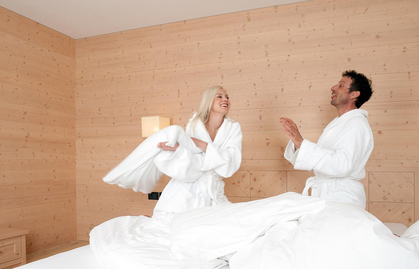 Couple laughing and teasing in the bedroom of Hotel Cavallino